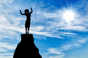Silhouette of a business woman at the peak of the mountain on the background of the sunny sky